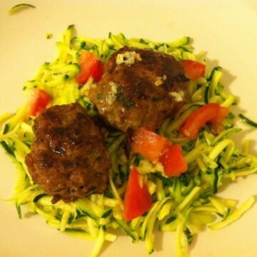 plate of healthy food with mini burgers and zucchini salad