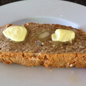 piece of paleo coconut flour macadamia nut banana bread topped with two slabs of butter