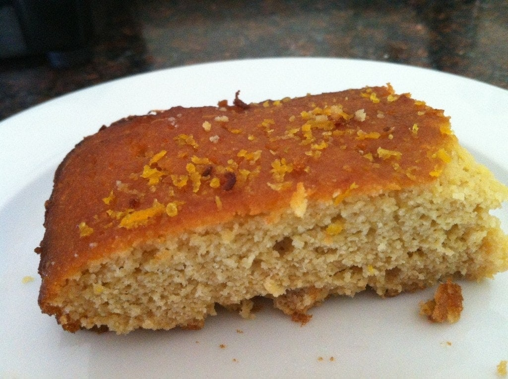 close up of a piece of orange cake on white plate