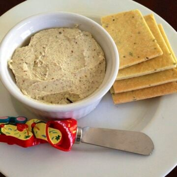 plate of homemade gluten free basil crackers next to a small serving dish with roasted garlic basil cheese dip