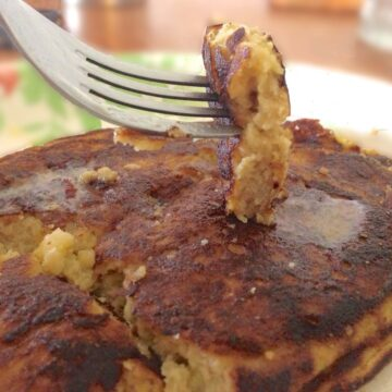 close up of stack of almond flour pancakes with one bite of pancake on a fork just above the stack