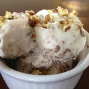 close up of small dish of paleo chocolate fudge swirl ice cream topped with chopped nuts