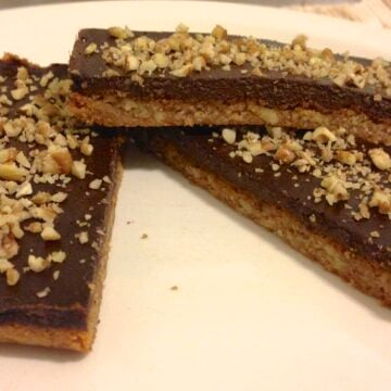 close up of three pieces of paleo chocolate pecan bars  topped with chopped up pecans