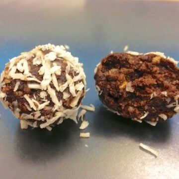 close up of two low carb paleo chocolate truffles with one piece opened up showing inside texture