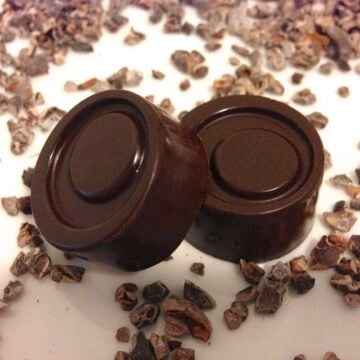 close up of two round pieces of homemade 84 percent dark chocolate with pieces of cacao nibs all around