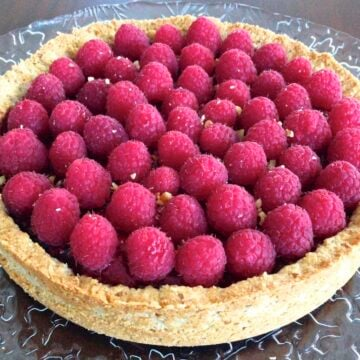 close up of large round paleo mix berry tart loaded with fresh raspberries