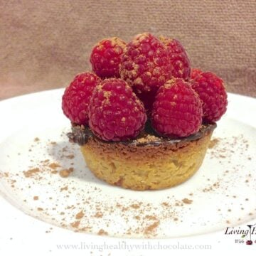 close up raspberry chocolate tart dusted with cacao powder on a round white plate