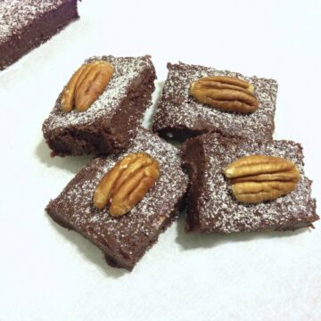 close up of four pieces of chocolate cherry fudge bars topped with one single pecan