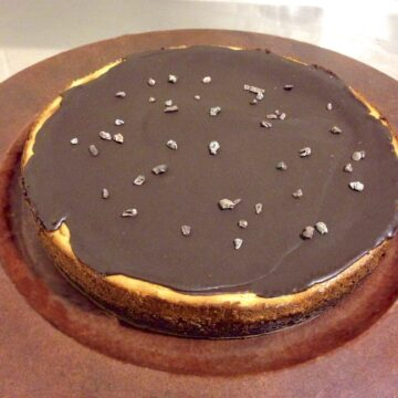 close up of large round paleo chocolate cheesecake topped with pieces of cacao nibs