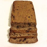 loaf of chocolate chip banana bread with three slices cut and laying down in front of the loaf