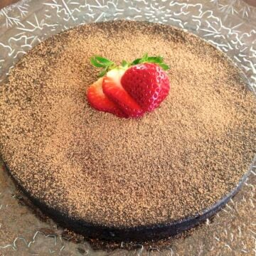 large round flourless chocolate torte dusted in cacao powder and topped with slices of fresh strawberries