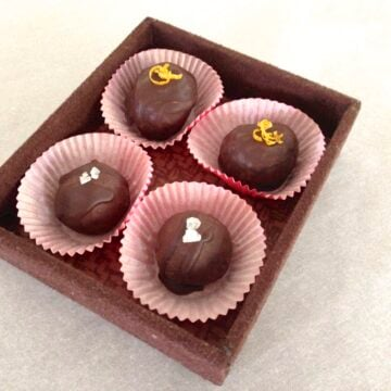 four handmade chocolate truffles in red paper cups sitting in a square serving dish