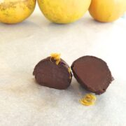 close up of dark chocolate orange truffle cut in half with three oranges in background