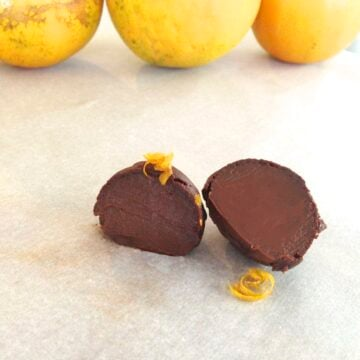 close up of dark chocolate orange truffle cut in half with three oranges in background