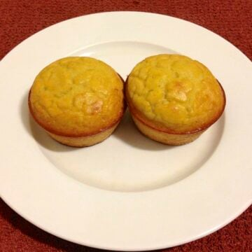 two coconut flour orange muffins on a round white plate