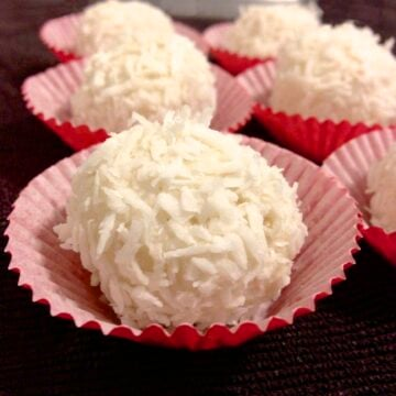 close up of several paleo coconut truffles in red paper cups and they are also known in Brazil as Brigadeiro