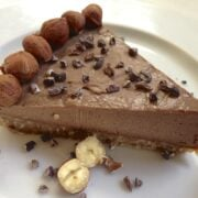 single slice of paleo hazelnut chocolate pie topped with cacao nibs