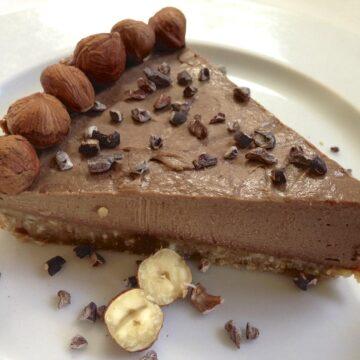 single slice of paleo hazelnut chocolate pie topped with cacao nibs