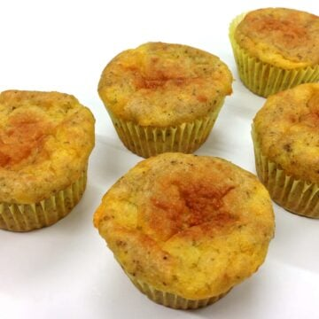 close up of five grain free cheesy oregano muffins on white surface