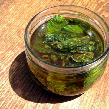 glass jar with peppermint leaves for making homemade peppermint oil