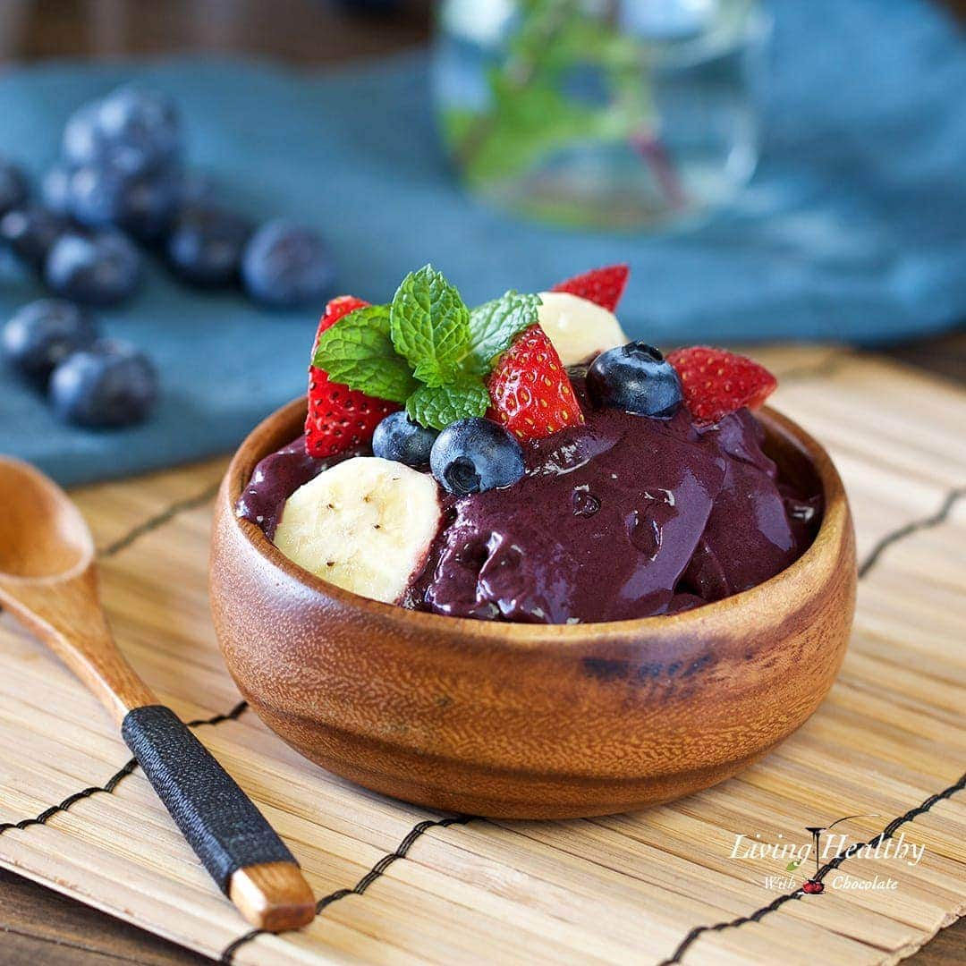 wooden serving bowl on bamboo placemat filled with traditional acai topped with fresh fruit