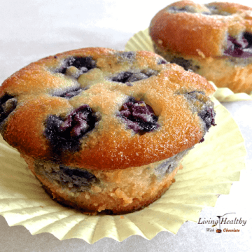 close up of two blueberry muffins in yellow paper muffin cup