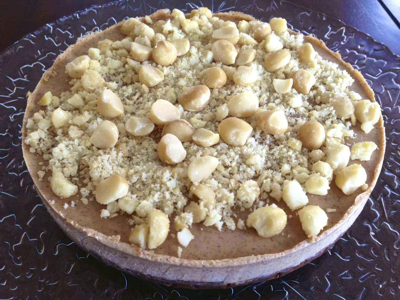 close up of a large complete paleo macadamia nut pie topped with full and chopped nuts