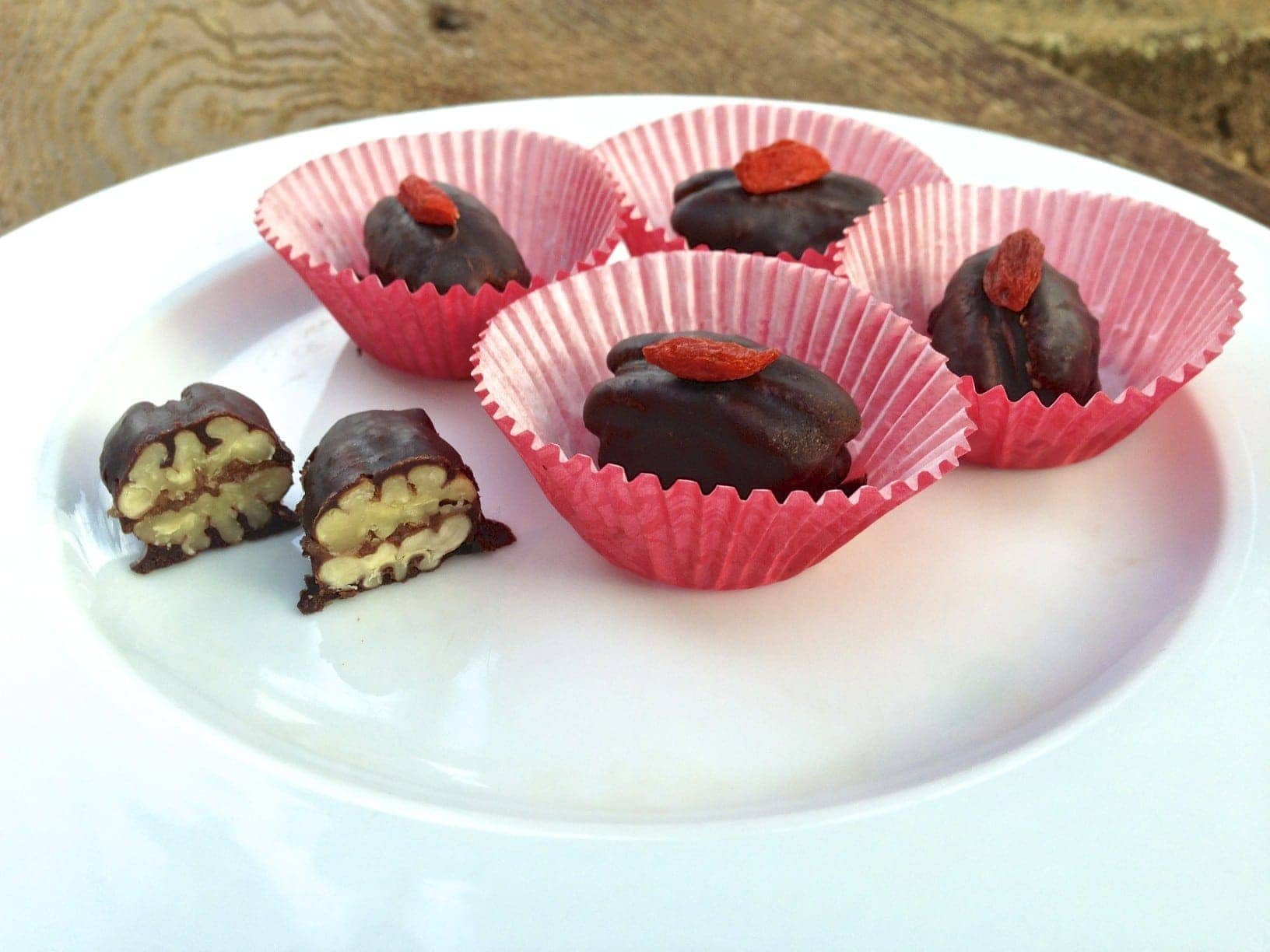 plate with chocolate caramel pecan candies in red paper cups with one by itself cut in half showing texture inside