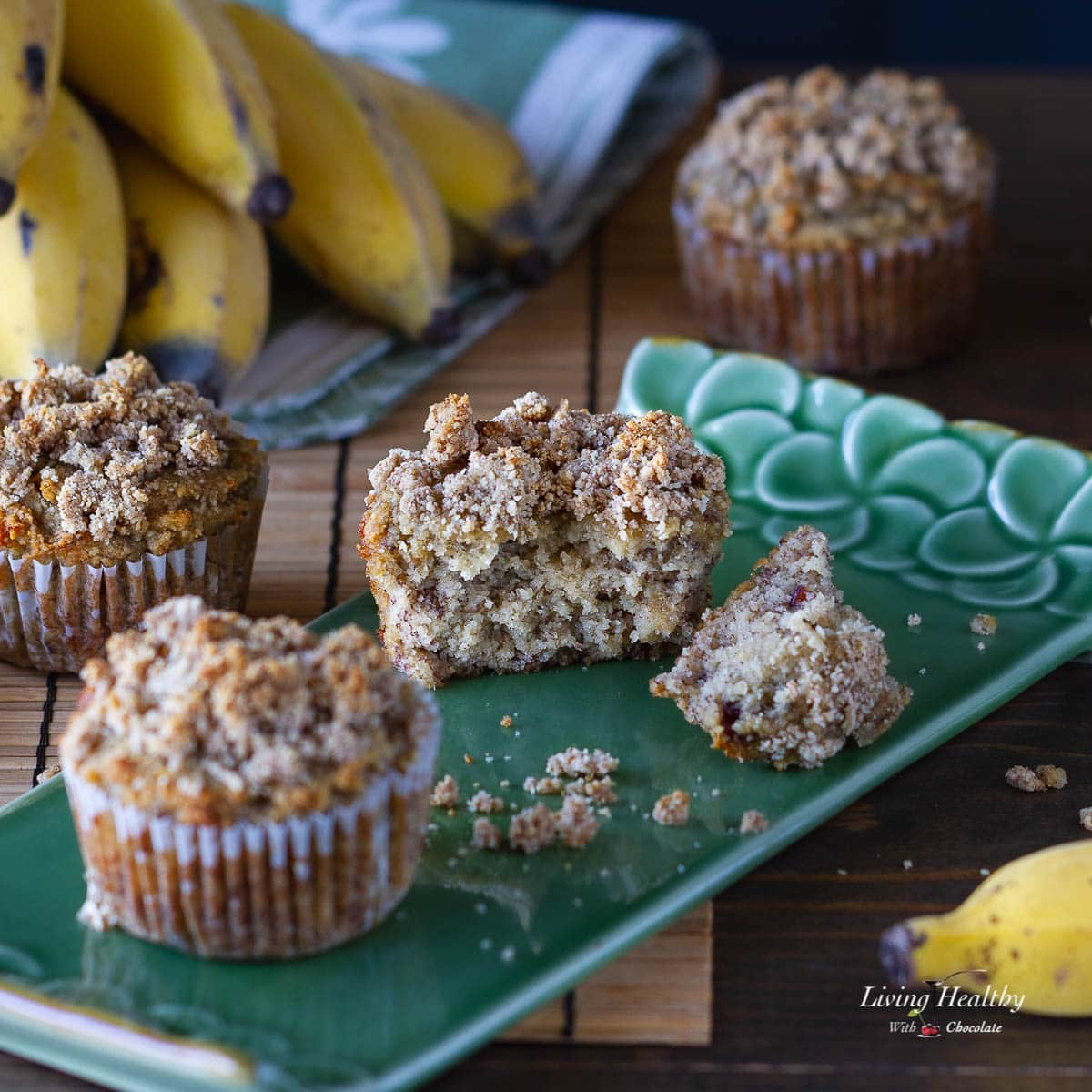 three banana muffins with crumb topping on a table and one muffin cut in half on a green plate