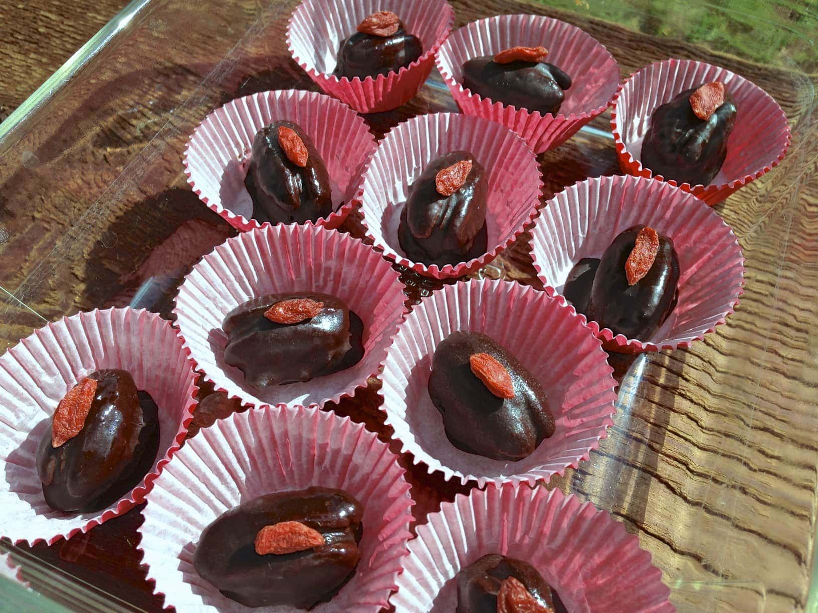several rows of chocolate caramel pecan candies in red paper cups