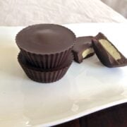 plate with stack of two paleo macadamia nut butter cups and one cup broken in half showing texture inside