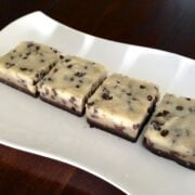 four square pieces of raw no bake chocolate chip cookie dough brownies on white plate with dark background