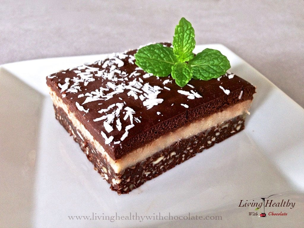 close up of chocolate macadamia triple layer brownie topped with shredded coconut and fresh mint
