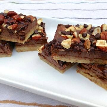 tray of paleo chocolate hazelnut cookie bars topped with chopped nuts