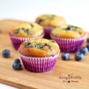 wooden cutting board topped with four coconut flour blueberry muffins in colorful muffin cups with loose blueberries around