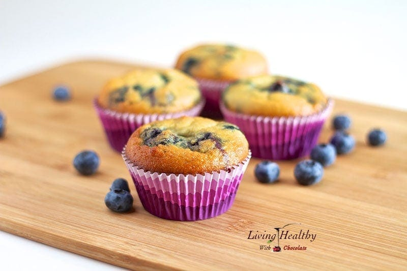 wooden table topped with four coconut flour blueberry muffins in colorful muffin cups with loose blueberries around