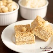 plate of paleo coconut macadamia nut bars with small dishes in background with macadamia nuts and shredded coconut