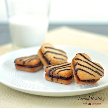 plate with four heart shaped vanilla cookies with creamy chocolate almond filling with tall glass of milk in background