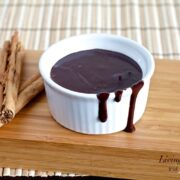 small white dish filled with paleo fudge sauce on wooden cutting board