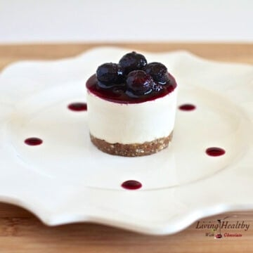 plate with a single serving raw no bake blueberry cheesecake topped with blueberry sauce and fresh blueberries