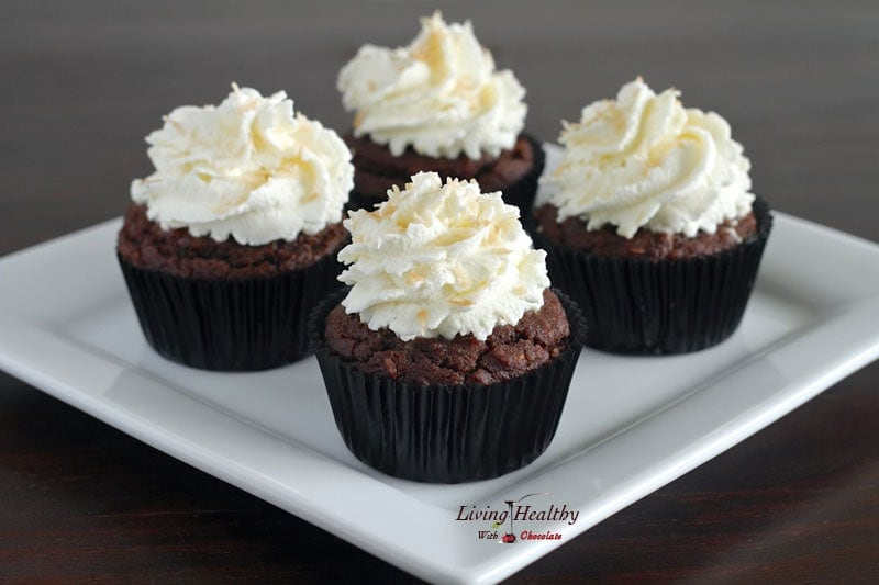 plate with four paleo coconut cupcakes topped with whipped cream