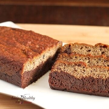 loaf of paleo black bottom banana bread on with three slices sitting sideways  on white plate