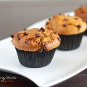 close up of two paleo flourless chocolate chip muffins on white plate.