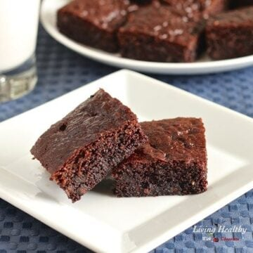 two paleo gluten free brownies with plate of more brownies and glass of milk in background