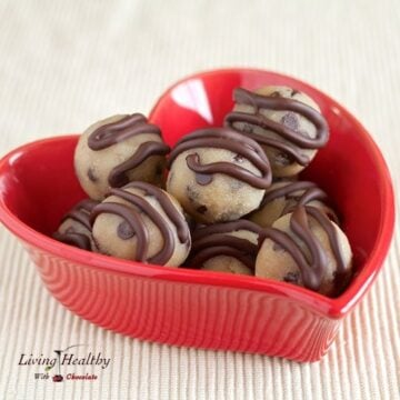 red heart shaped bowl with paleo gluten free cookie dough bite topped with stripes of chocolate
