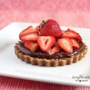close up of homemade paleo nutella strawberry tart topped with slices of fresh strawberries and chocolate ganache