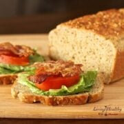loaf of homemade paleo sandwich bread on cutting board with two slices topped with bacon lettuce and tomato