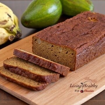 loaf of avocado banana bread on cutting board with bananas and avocado in background