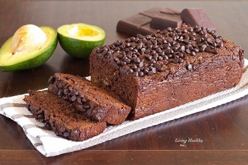 loaf of paleo avocado chocolate bread topped with loads of chocolate chips and more chocolate and avocado in background