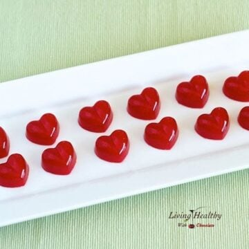 red heart shaped homemade fruit snacks rectangular plate on green placemat